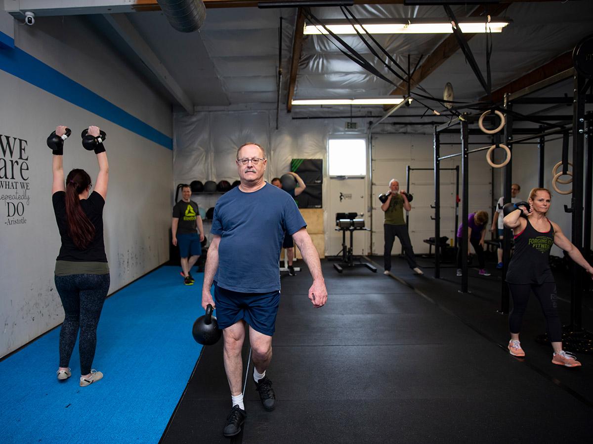 The Quad gym, man lifting kettle bells