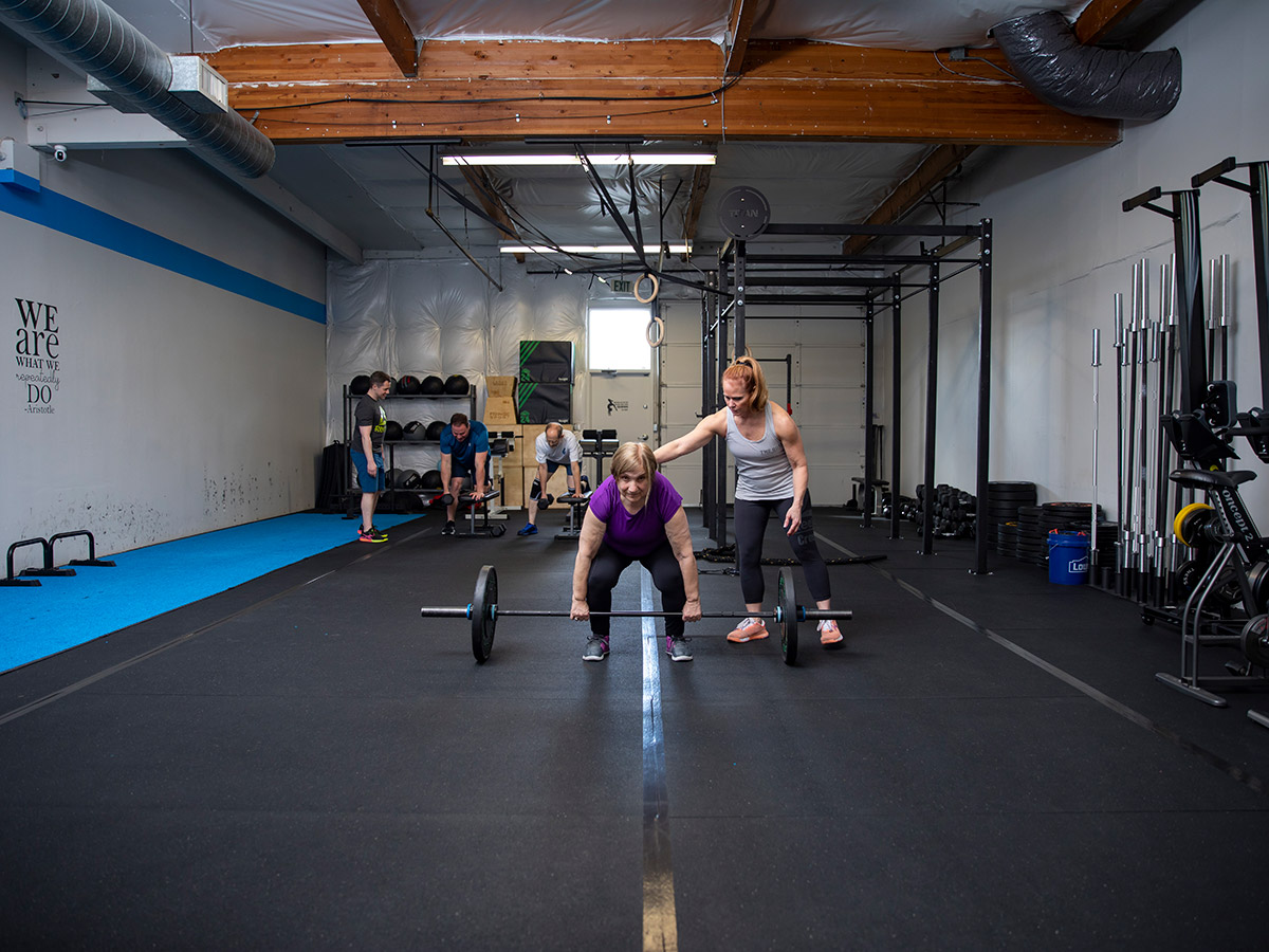 The Quad gym, woman doing weight lift with trainer